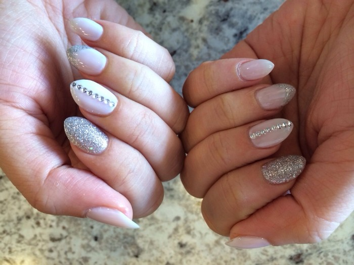 glitter in silver, and matching rhinestones, decorating the white, short stiletto nails, of two hands