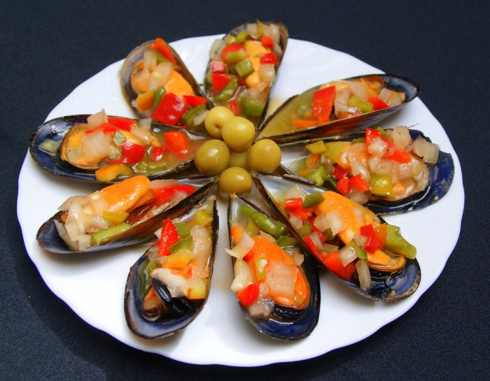 mussels cooked in their shells, with chopped vegetables and green olives, hor dorves, served in a round plate