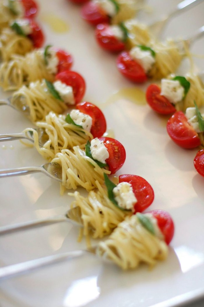 spaghetti wrapped around several forks, and topped with fresh basil leaves, cheese and cherry tomatoes