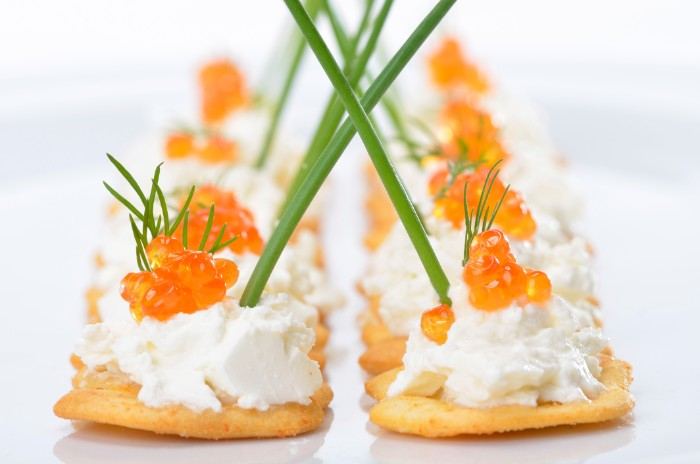 thin crackers with creamy, white spread and red caviar, hor dourves garnished with chives, and sprigs of dill