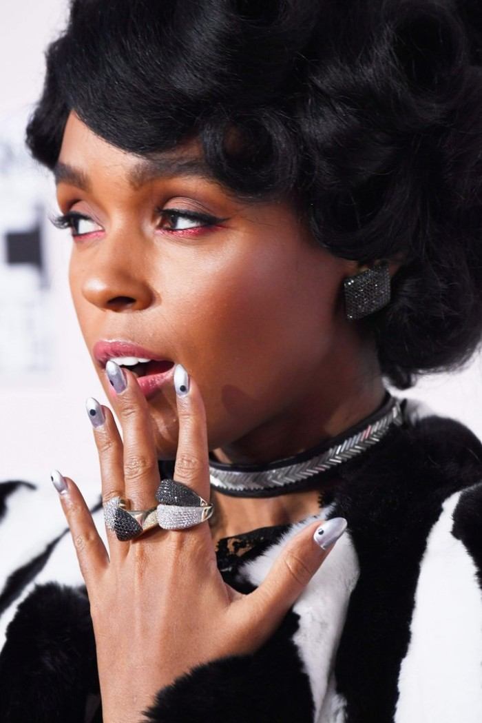 silver metallic nail polish, decorated with small black dots, worn on stiletto nails, belonging to janelle monae