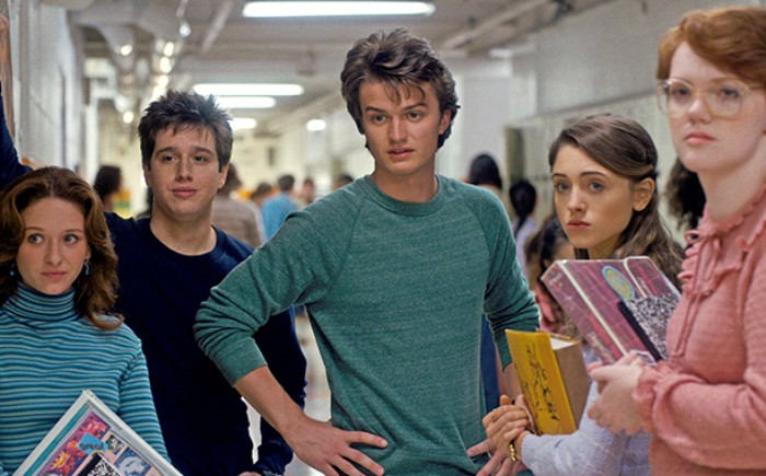 steve harrington played by joe keery, dressed in a greenish-blue sweater, with a wavy quiff hairdo, 80s costumes