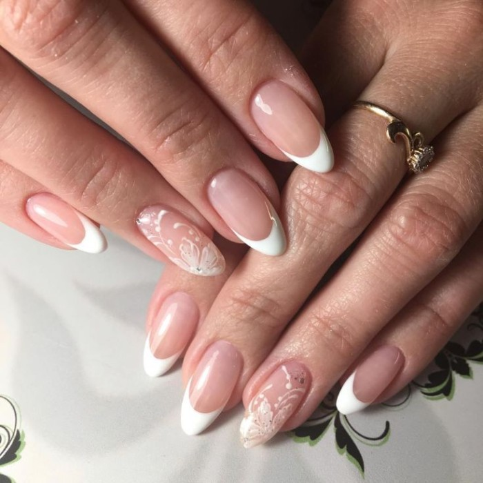 floral motifs in white, painted on the ring finger nails, of two hands with stiletto nails, and classic french manicure