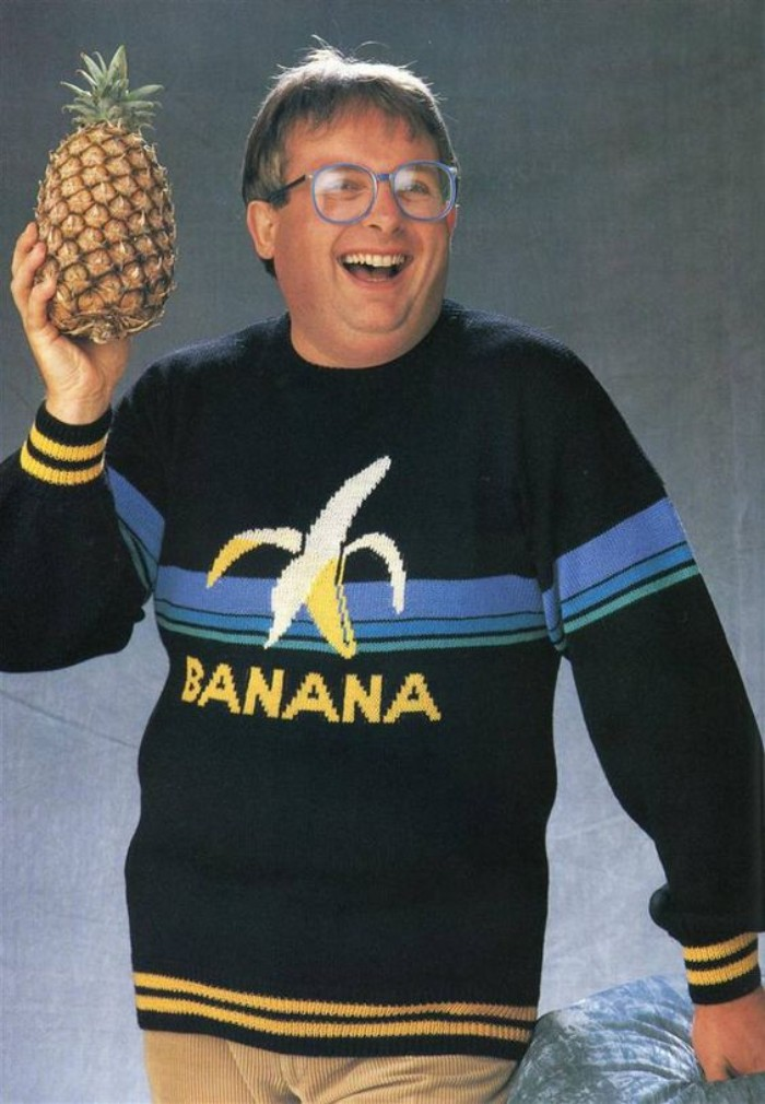sweater in black, yellow and blue, with a picture of a banana, and the word banana in yellow, 80s outfits guys, worn by a laughing man, with glasses, holding a pineapple