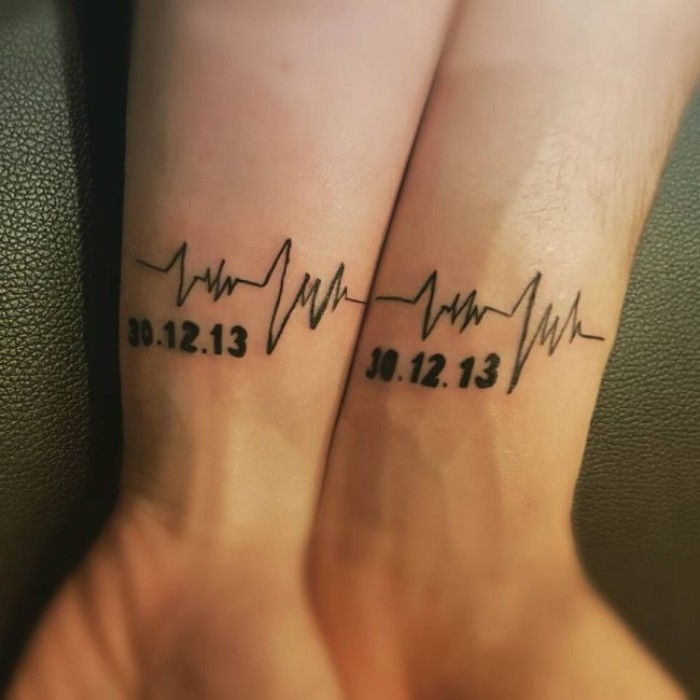 husband and wife tattoos, life line and a date, tattooed in black, on the wrists of two hands, placed next to each other