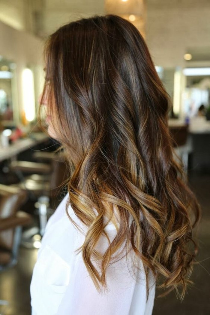 loose curls on long brunette hair, worn by a woman dressed in white, balayage dark hair, with honey blonde highlights