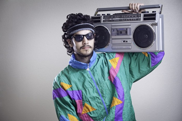 teal jacket with yellow and light blue, pink and purple geometric shapes, worn by a man with dark curly hair, a headband and sunglasses, 80s clothes, holding a boombox