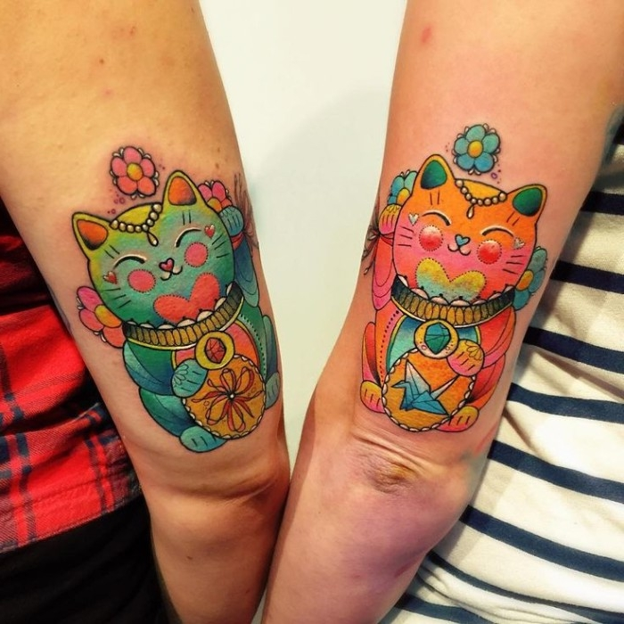 japanese-inspired waving cat tattoos, identical maneki-neko design, done in different colors, above the elbows of two arms