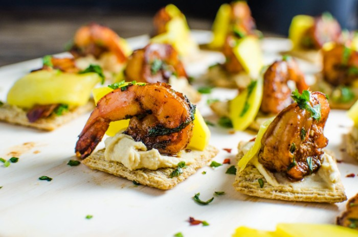 square crackers with hummus, topped with mango, and grilled prawns, hour derves sprinkled with fresh, chopped green herbs