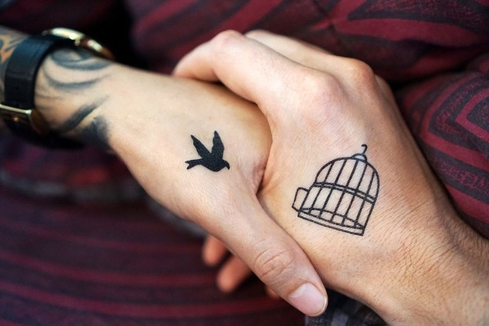 bird in flight, tattooed in black on a hand, held by another hand, with a black bird cage tattoo, matching tattoos with symbolic meaning