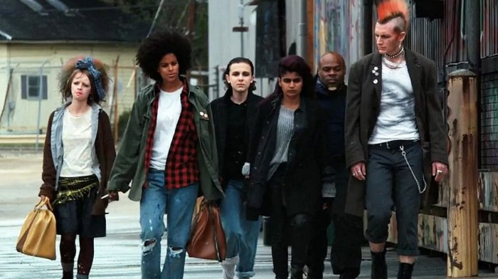 tall man with red mohawk hair, dressed in punk clothing, surrounded by young people, dressed in 80s costumes, jeans and plaid shirts