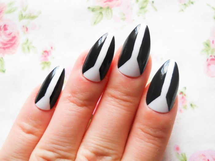 dual color manicure, in black and white, on almond shaped nails, seen in close up, on a floral background