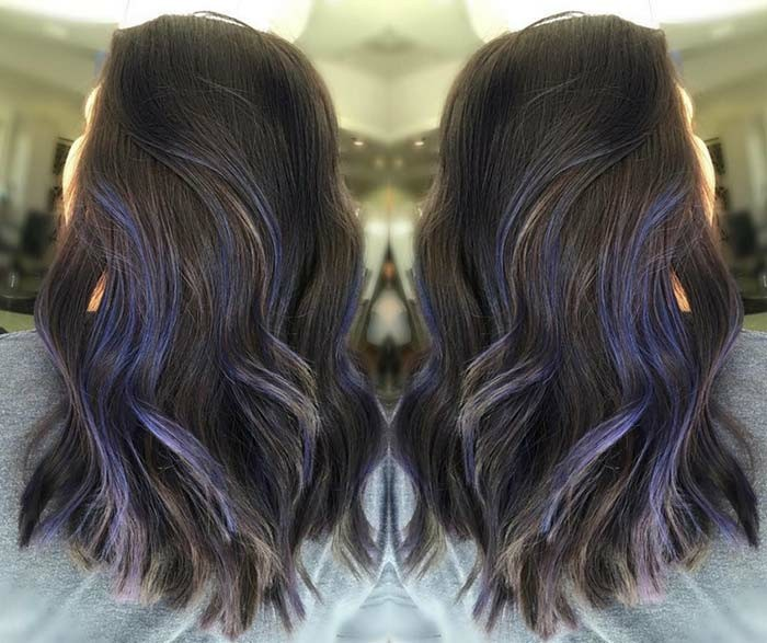 blue strands of hair, decorating a wavy, medium length dark brunette hairdo, balayage brown hair, seen in two imrrored images