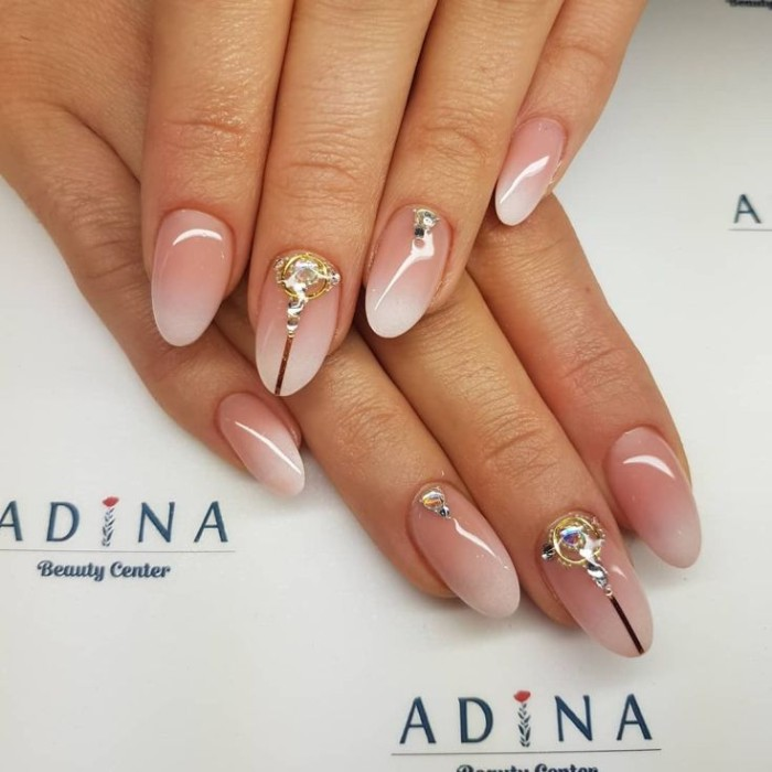 smooth and glossy oval shaped nails, decorated with gold and silver rhinestones, and featuring an ombre effect french manicure
