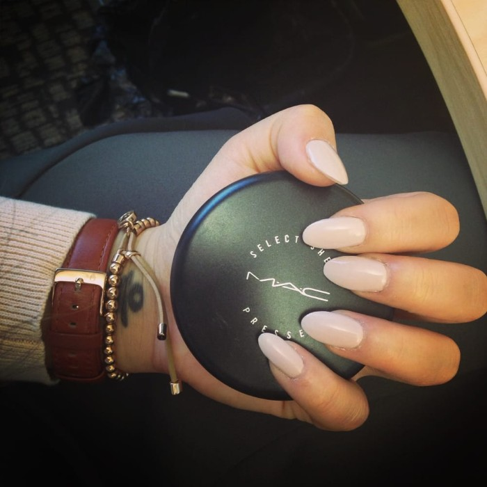 make up case in black, held by a hand with long, oval nails, painted in a milky, pale pink nail polish