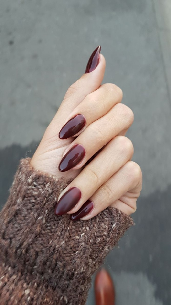 dark burgundy red nail polish, on acrylic nail shapes, worn by a pale hand, dressed in a brown, chunky knitted sleeve