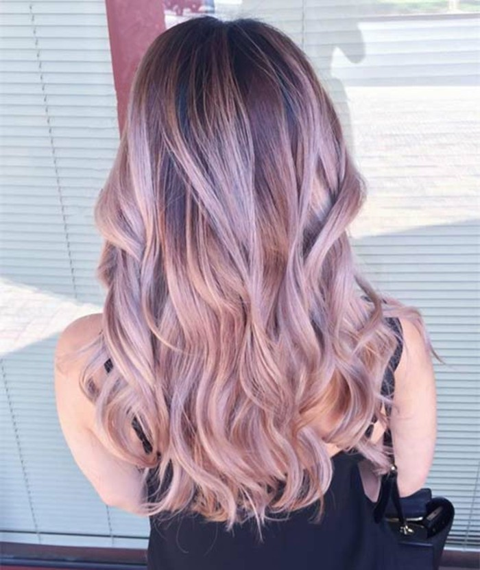 pastel pink balayage brown hair, with loose curls, worn by a woman in a black strappy top, with a bag on her shoulder