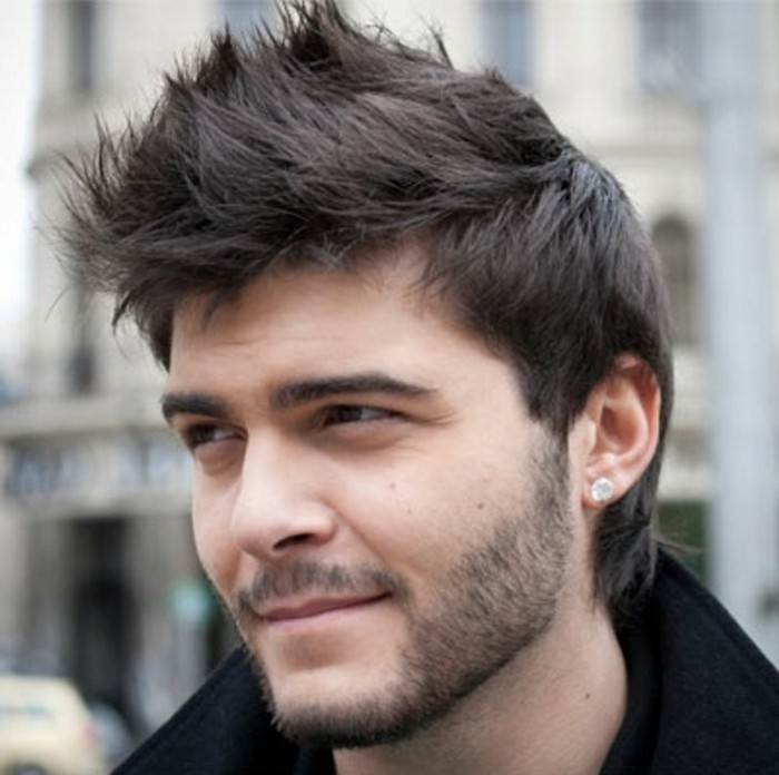 thick black hair, styled in faux hawk, trendy haircuts for men, worn by a pale young man, with short mustache and beard