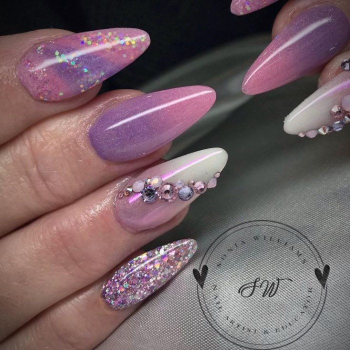 violet and pink nail polish, decorated with glitter, and iridescent rhinestones, on a long and sharp amnicure, seen in close up