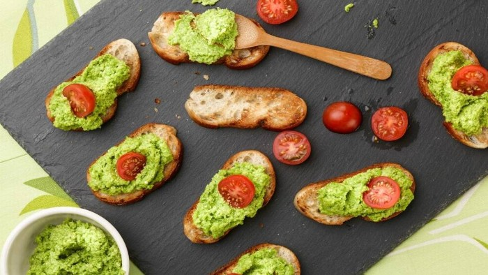 guacamole spread on several pieces of toasted bread, some are garnished with cherry tomatoes, cut in half, hors d oeuvres recipes, with fresh avocado