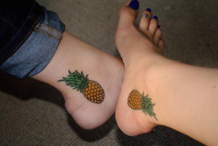 orange and green tattoos, done between the ankles and heels of two feet, and depicting two identical pineapples, matching sister tattoos, one foot has dark blue nail polish, and a toe ring
