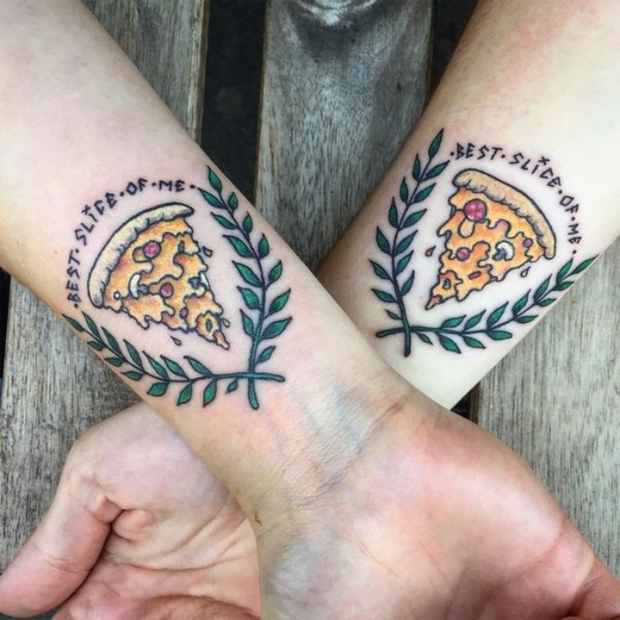 laurel leaves surrounding a pizza slice, accompanied by the inscription best slice of me, matching bestfriend tattoos, in full collor, on the wrists of two crossed arms