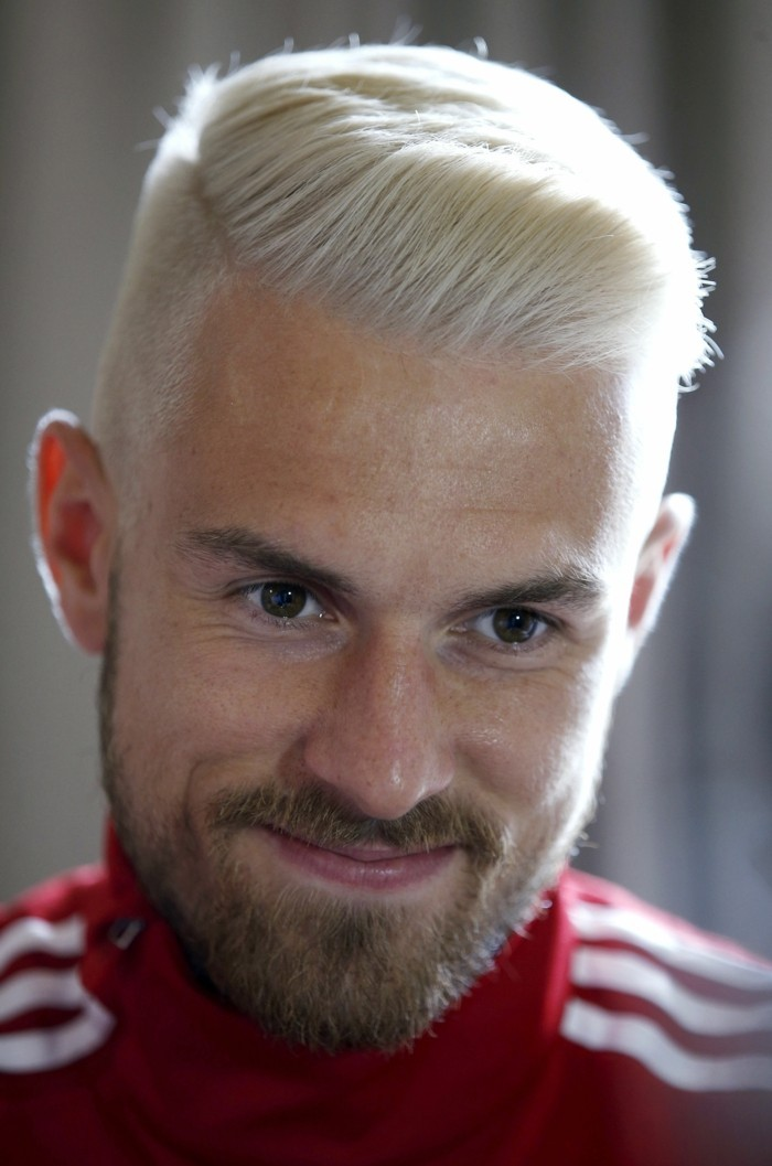 red adidas tracksuit top, worn by a smiling man, with mustache and a beard, and platinym blonde hair, styled in a quiff