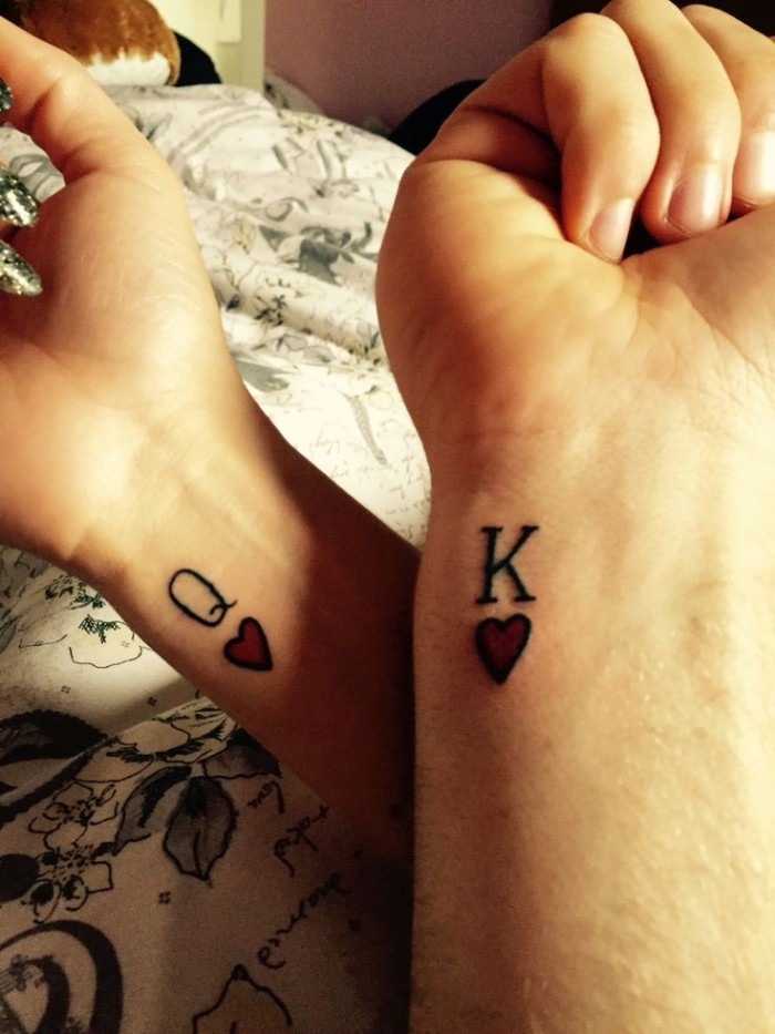 symbols for queen and king of hearts, from playing cards, tattooed on the wrists of two hands, matching tattoos for couples in love, red and black ink