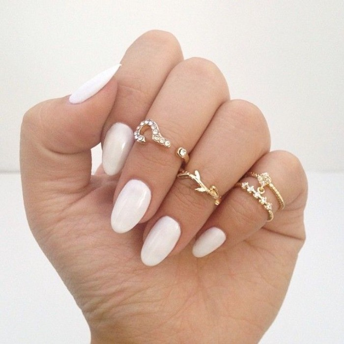 clear white nail polish, on pale fingers, decorated with several golden rings, almond nail designs, for everyday wear