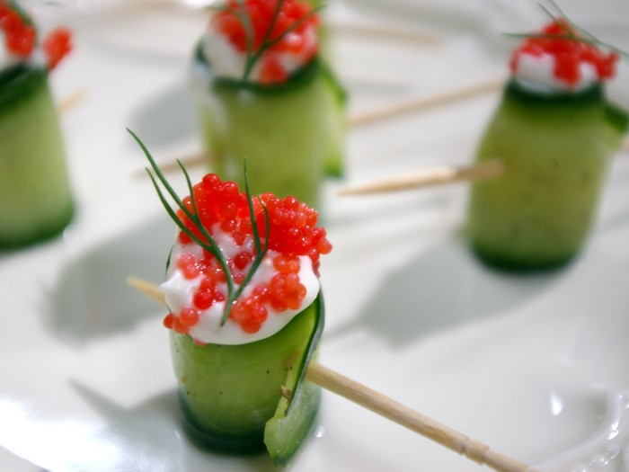 cucumber rolls stuffed with white sauce, red caviar and dill, hors dourves, skewered and placed on a white plate