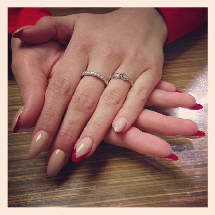 nails painted in nude beige on the outside, and red on the inside, and featuring small red details, long oval manicure, on pale slim hands