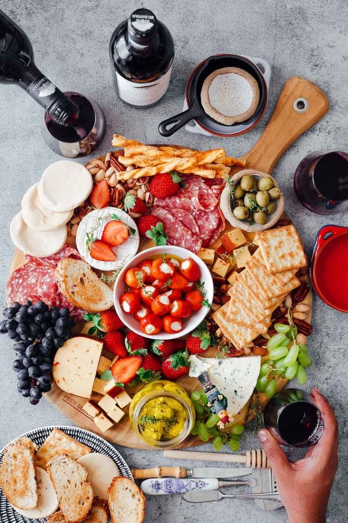 rich selection of appetizers, on a round wooden board, salami and cheeses, crackers and olives, fresh fruit and bread sticks, wine bottles and glasses