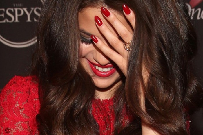lace dress in red, and matching red lipstick and nail polish colors, worn by smiling selena gomez, with classic almond-shaped manicure