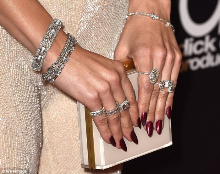 clutch bag in white and gold, held by two hands, with several rings and bracelets, pointy nails in dark shiny red