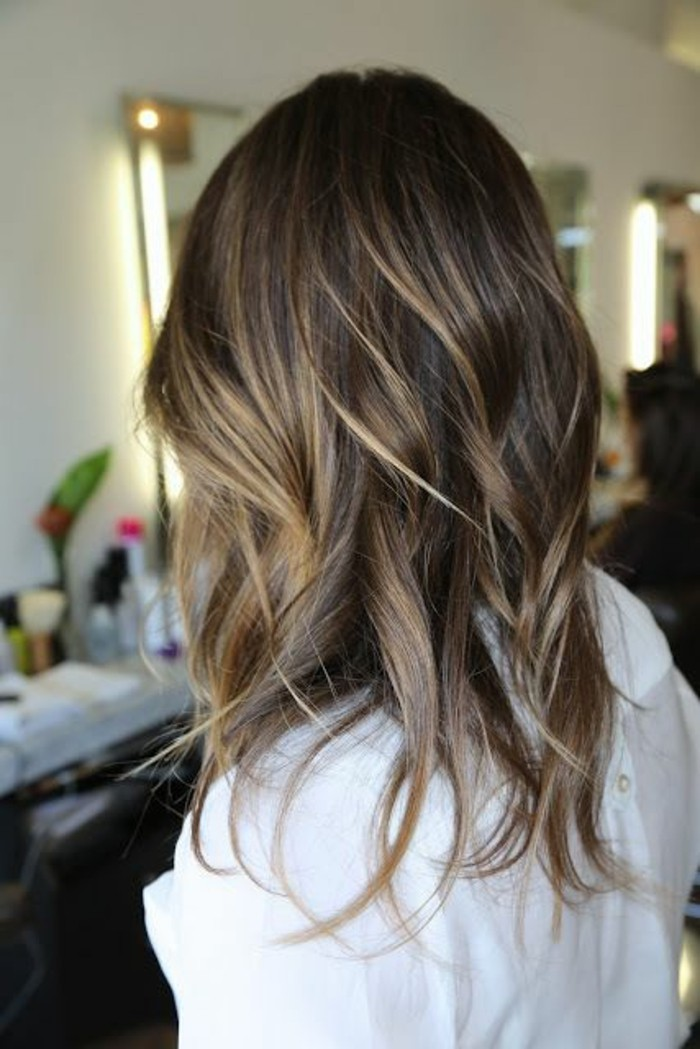 ash-blonde highlights, on wavy brunette hair, worn by a woman dressed in white, balayage dark hair, seen from the back
