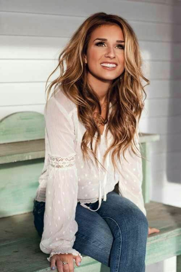 jeans and a white lacy top, worn by a smiling woman, with blonde balayage, sitting on a worn pale bench