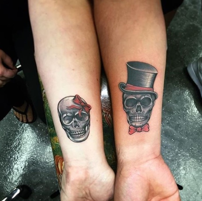 top hat in black and red, and a red bow tie, on a skull, tattooed near the wrist of an arm, his and hers tattoos, the arm next to it also features a skull tattoo, decorated with a red head bow