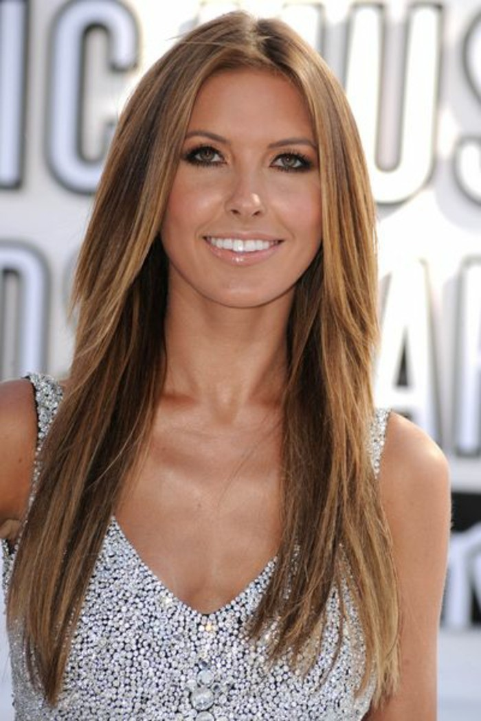 straightened layered hair, in light brunette, with a dark blonde balayage, worn by a smiling woman, in a sparkling silver dress