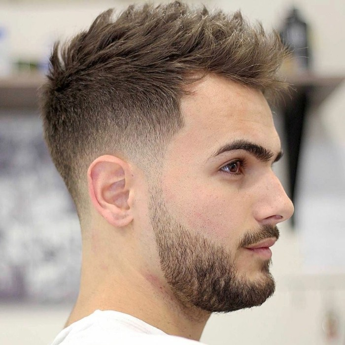 chectnut brown hair, styled in a spiky faux hawk, types of haircuts for men, worn by a young man, with a mustache and a beard