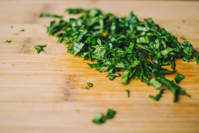 chopped fresh basil, on a wooden cutting board, seen in extreme close up, horderves step by step