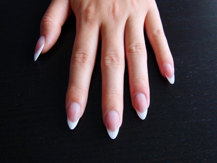 simple french manicure, on a hand with long finhers, and pointy nails, resting in a dark surface