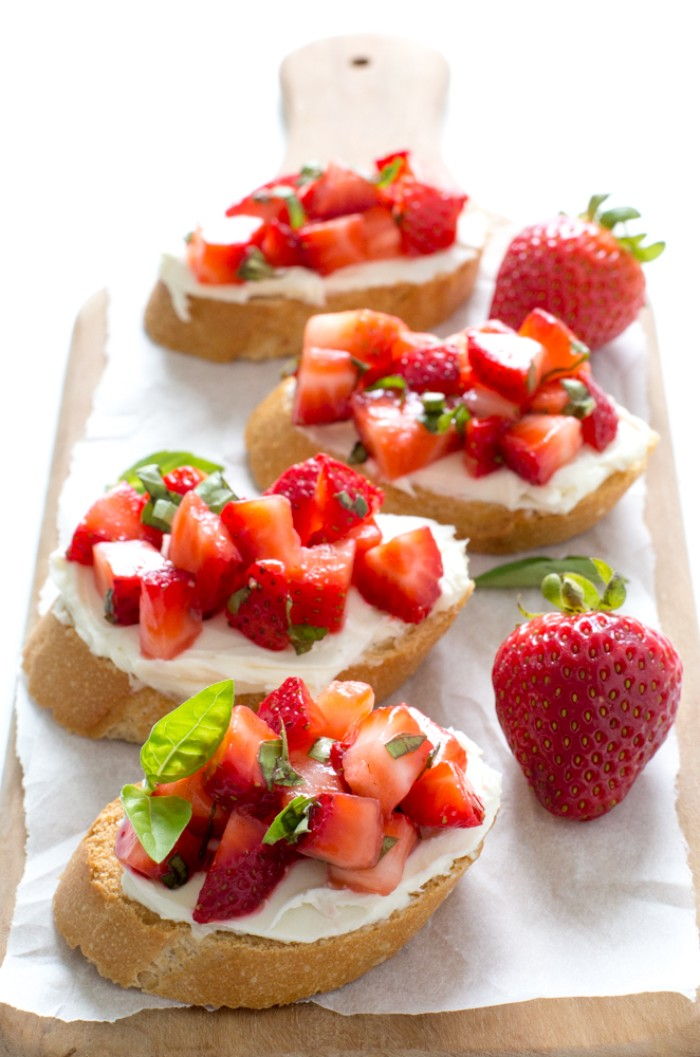 four bruschetta with ricotta, chopped strawberries and basil leaves, hor d oeuvres, placed on a wooden chopping board