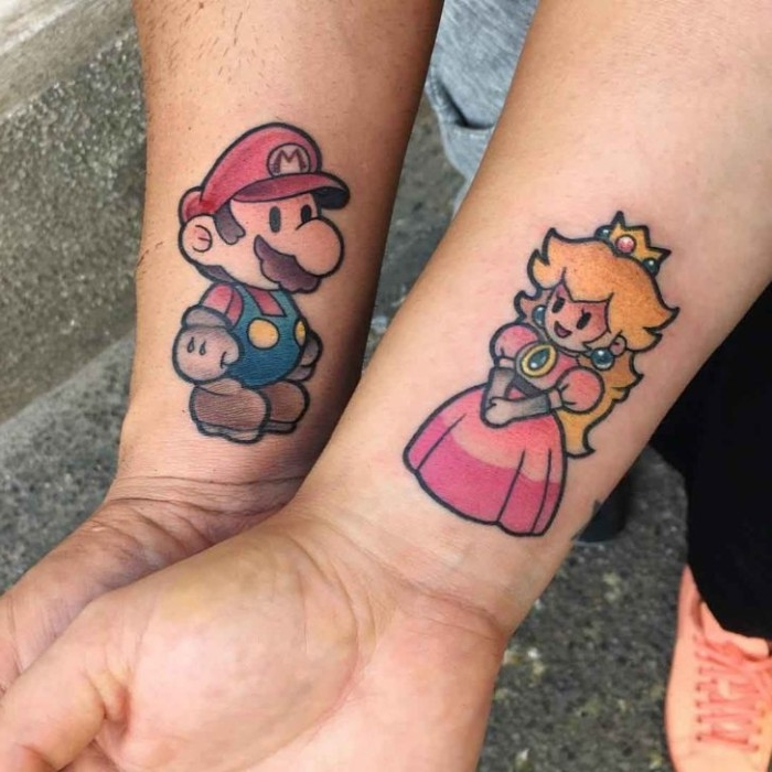 his and hers tattoos, princess peach and super mario tattoos, done in full color, near the wrists of two arms