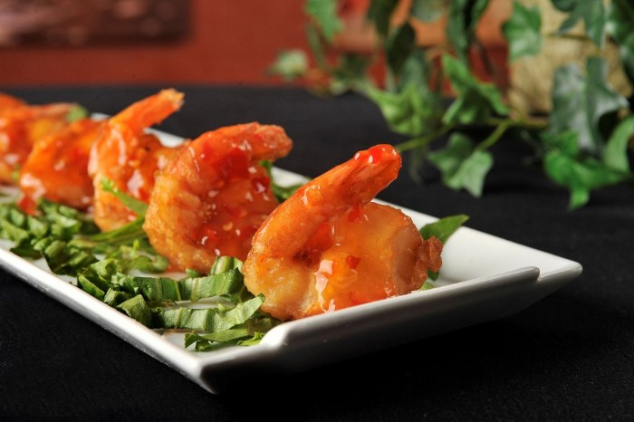 rectangular white plate, containing chopped leafy green veg, and several prawns, with sweet chili sauce, hors dourves