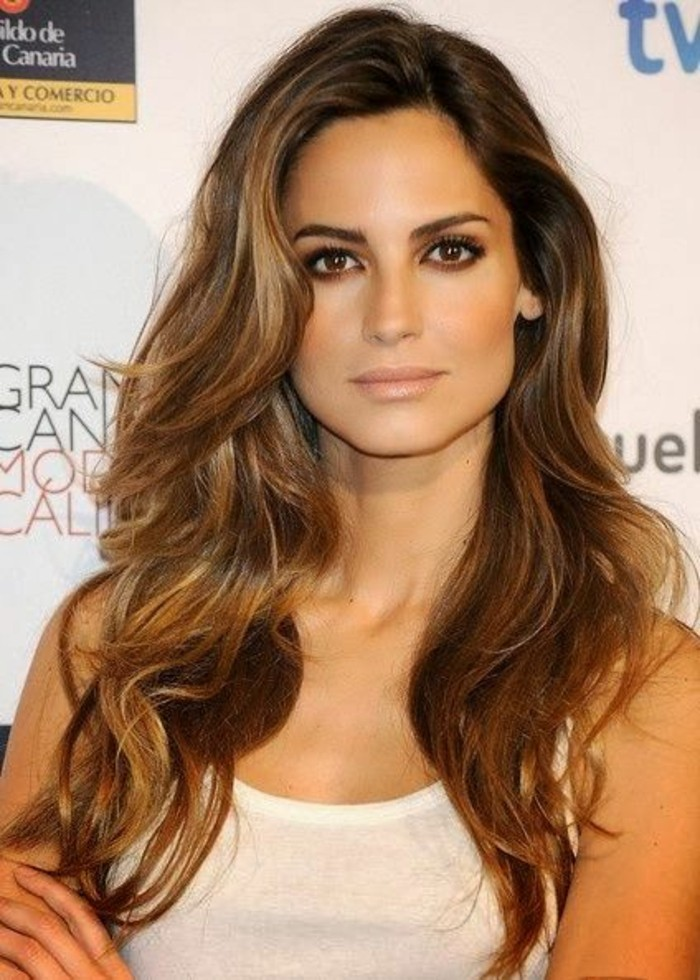side-parted wavy brunette hair, with caramel balayage, on a young woman, with dark eyes, wearing a white tank top