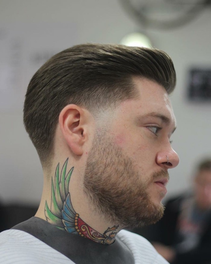 nose ring and colorful tattoo, worn by a young man, with short hair, featuring a pompadour like detail, trendy haircuts for men, worn with short beard and mustache
