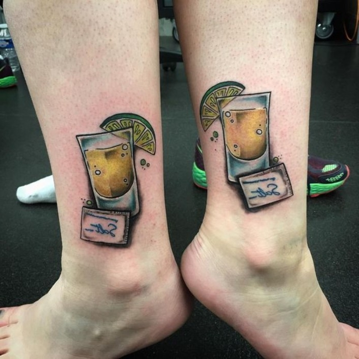 lime wedge on a tequila shot, with a small pack of salt nearby, matching friend tattoos, done in full color, on the ankles of two legs
