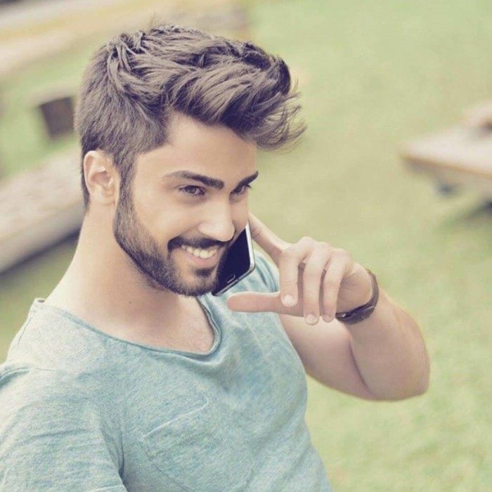 trendy haircuts for men, smiling young man, with a moustache and a short beard, holding a phone to his face, brunette textured cut