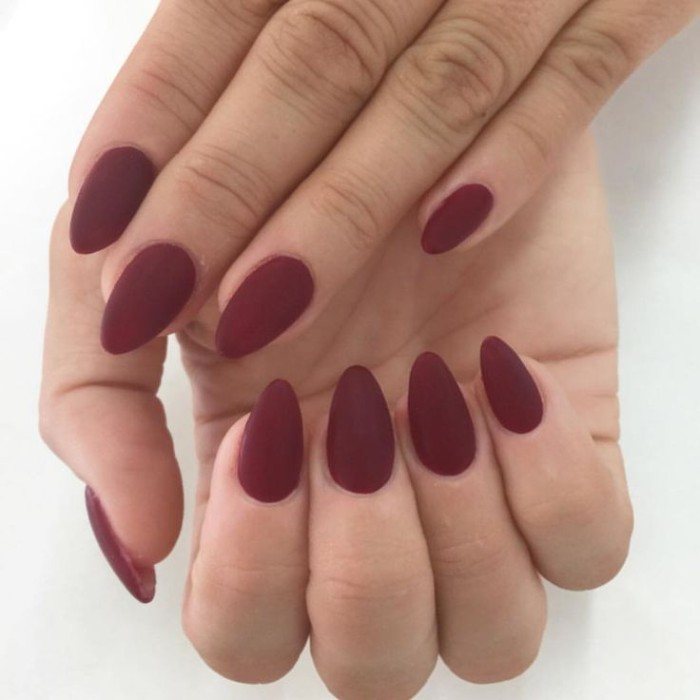oxblood matte nail polish, on the short, pointy nails of two hands, seen in a close up, manicure ideas