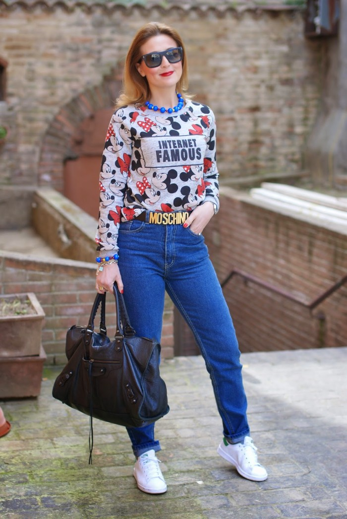 sweater in pale grey, with mickey and minnie mouse print, worn by a blonde woman, in blue jeans, holding a large leather bag, 80s outfits, sunglasses a moschino logo belt